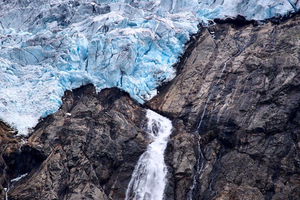 Blue ice and a small waterfall with melted water at the edge of Folgefonna glacier on a mountain side in Norway