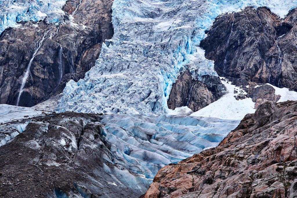 Ice formations, between the mountain sides, of the blue compressed ice on Folgefonna glacier in Norway