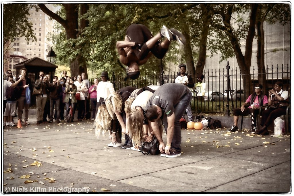 Street performer doing a somersault over a row of tourists